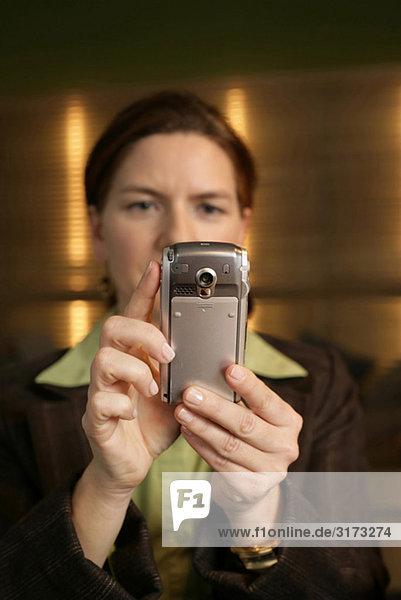 Frau hält ein Handy in der Hand