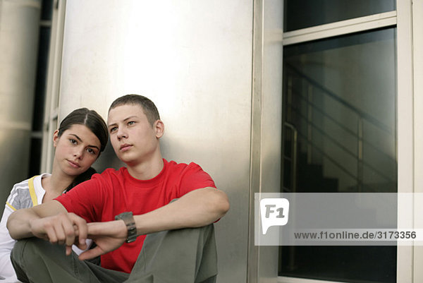 Teenage couple sitting in front of a office building x4ga9-1421