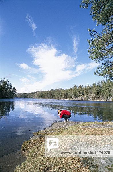 Eine Frau Trinkwasser in einem See  Schweden.