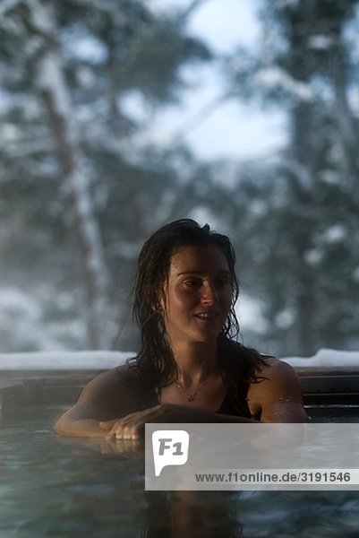 Eine Frau mit ein heißes Bad außerhalb im Winter  Schweden.