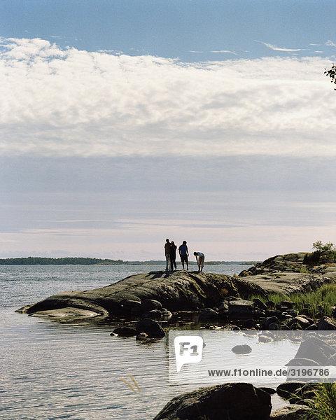 Vier Menschen stehen auf eine bloße Klippe  Harstena  Gryt Archipels  Östergötlands  Schweden.
