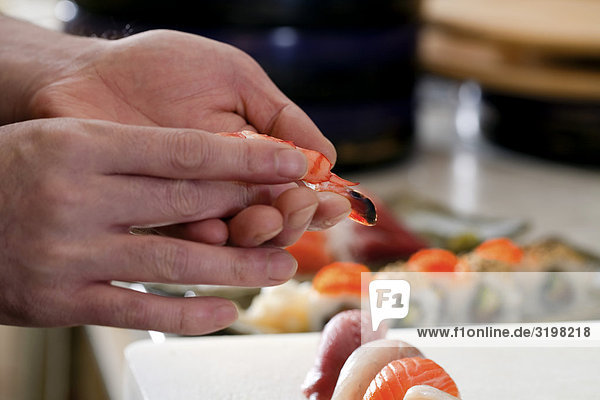 close-up of japanese chef making sushi