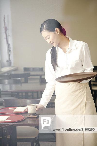 Porträt der jungen japanischen Kellnerin Einstellung Tisch im restaurant