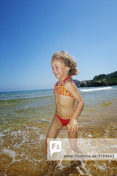 kleines Mädchen ausgeführt durch Brandung am Strand