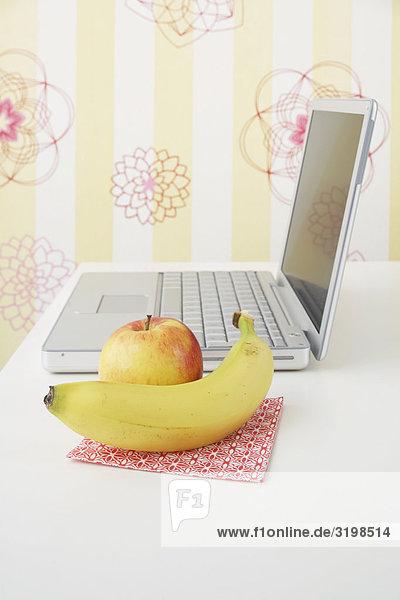 Stillleben von Apple und Banane mit Laptop auf Tabelle