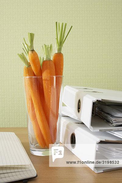Karotten in Glas auf Schreibtisch