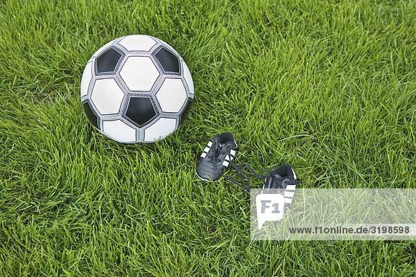 Stillleben mit Ball und winzigen Fußballschuhe