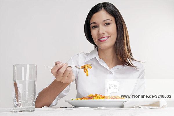Frau Essen Pasta und lächelnd
