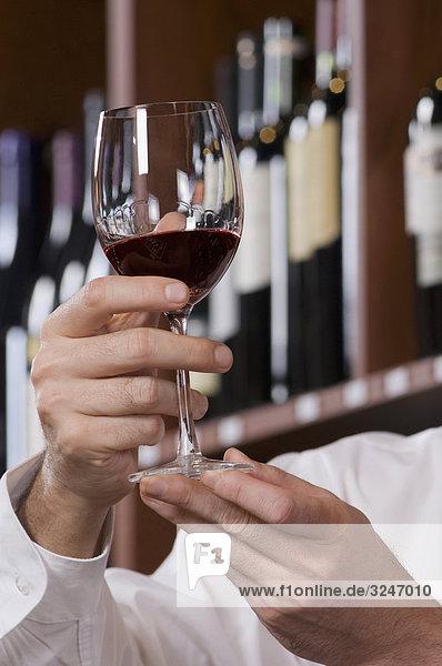 Mann  der ein Glas Wein in einer Bar hält