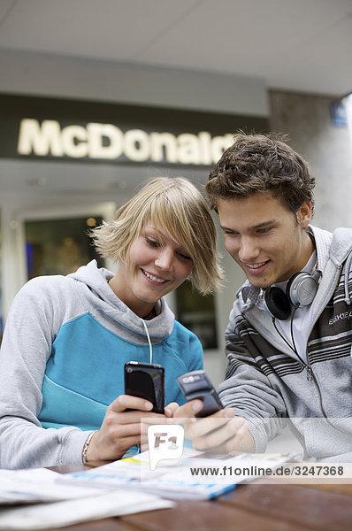 Zwei Teenager amüsieren sich über Handyfotos  Frontalansicht