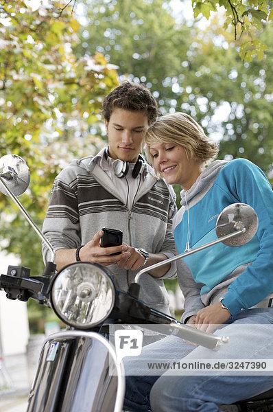 Zwei Jugendliche mit Mofa Mobiltelefon nutzend  Hochformat