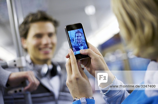Junger Mann wird in U-Bahn mit Mobiltelefon fotografiert  Schrägansicht