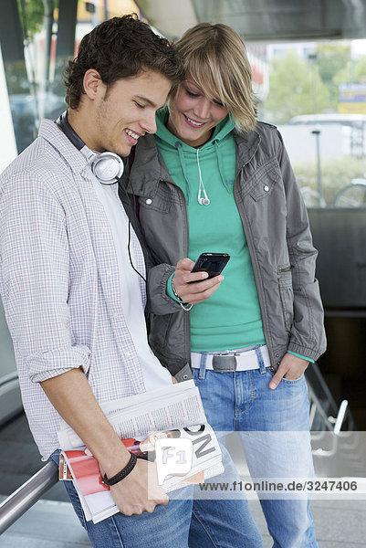 Teenagerpaar vor Rolltreppe Handy benutzend  Dreiviertelansicht