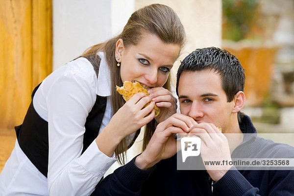 Young couple eating sandwiches on the street