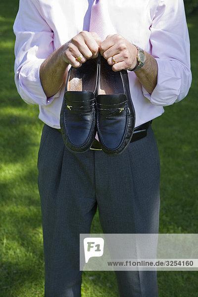 Ein Unternehmer hält ein Paar Schuhe  Stockholm  Schweden.