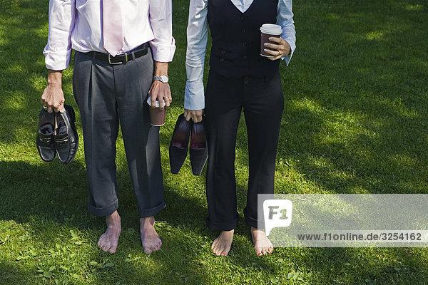 A barfuß Geschäftsmann und ein barfuß geschäftsfrau stehend auf Gras  Stockholm  Schweden.