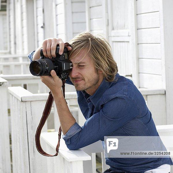 Ein junger Mann mit einer Kamera  Skane  Schweden.