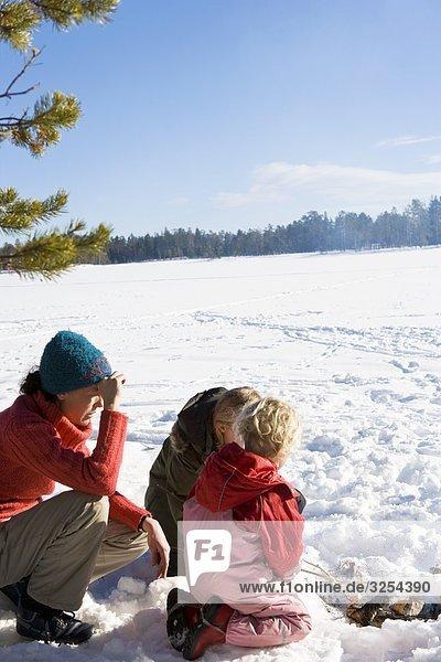 Mutter und Töchter mit einem Picknick im Schnee  Schweden.