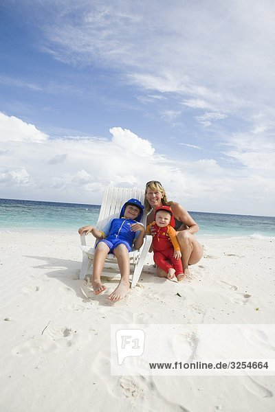 Portrait of a mother with two children on a beach  the Maldives.