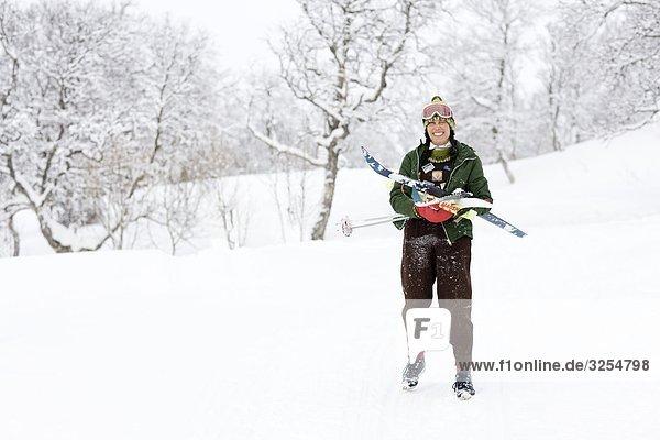 Frau trägt Ski in winterlichen Landschaft  Schweden.