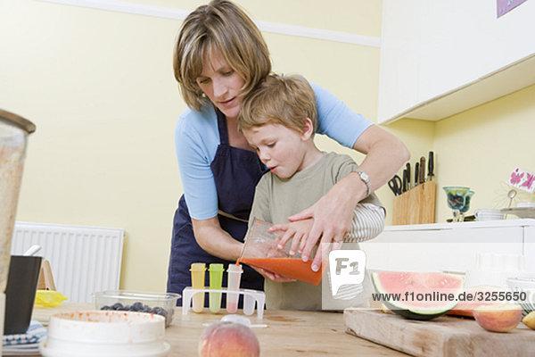 Junge und Mutter machen Obst-Lollies.