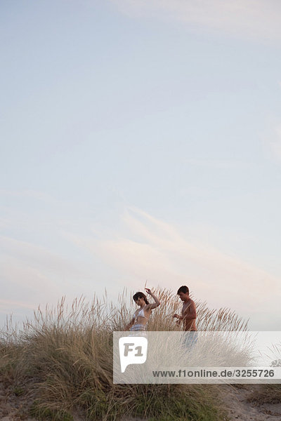 couple playing in the reed at the beach