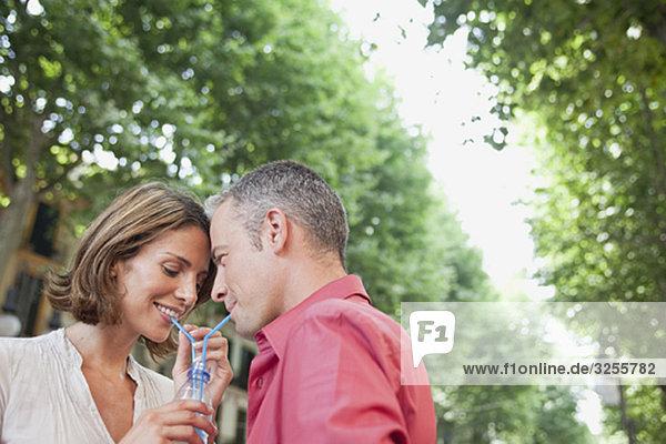 Paar trinkt aus dem gleichen Glas