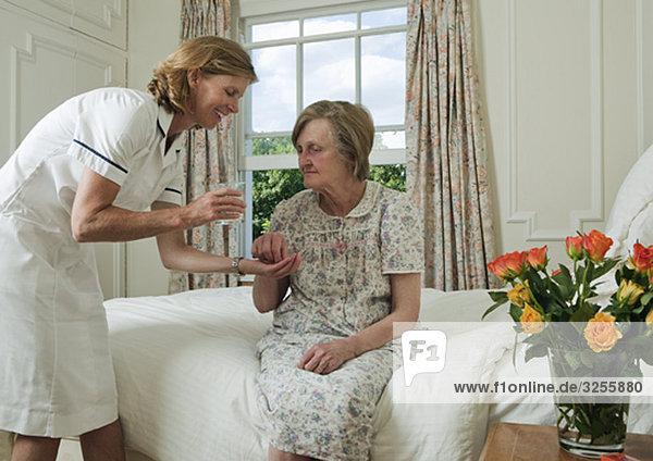 Ältere Frau nimmt Pille von der Krankenschwester