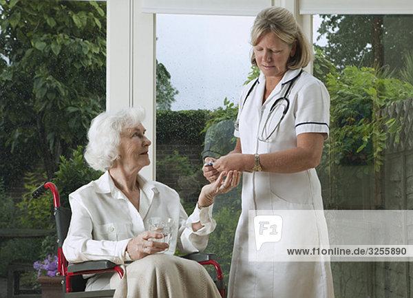 Krankenschwester verteilt Medikamente an die Frau