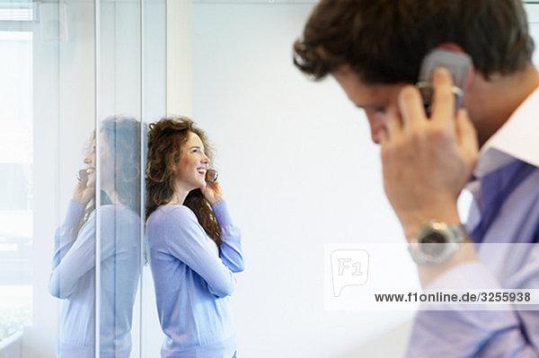 Geschäftsmann und -frau am Telefon