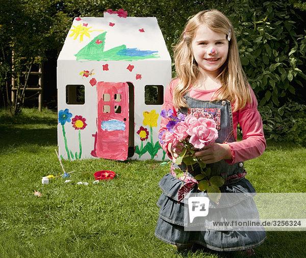 Ein Mädchen mit Blumen und einem Frauenhaus.