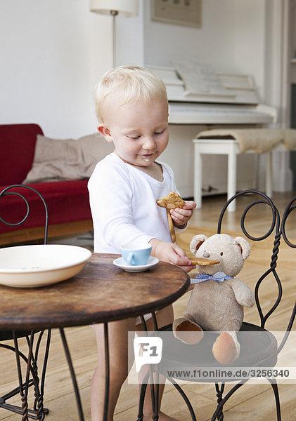 Kleinkind mit seinem Teddy auf der Teeparty