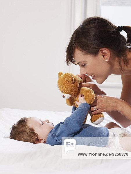 Mutter und Baby spielen mit Teddybär