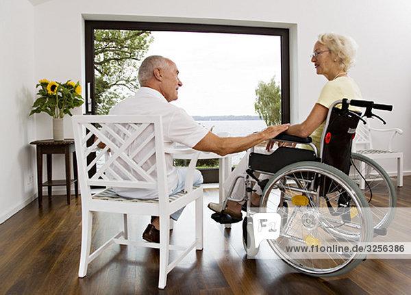 Mann berührt Frau im Rollstuhl