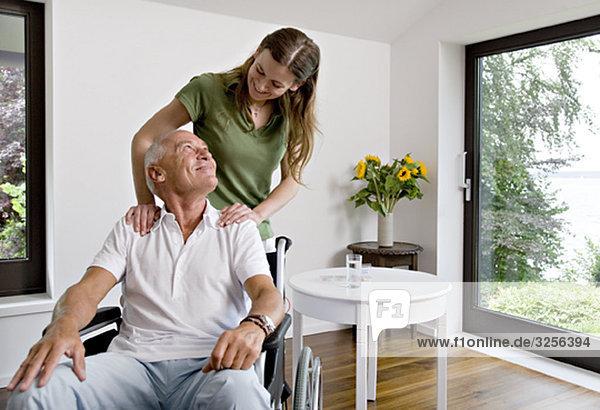 Frau berührt Mann im Rollstuhl