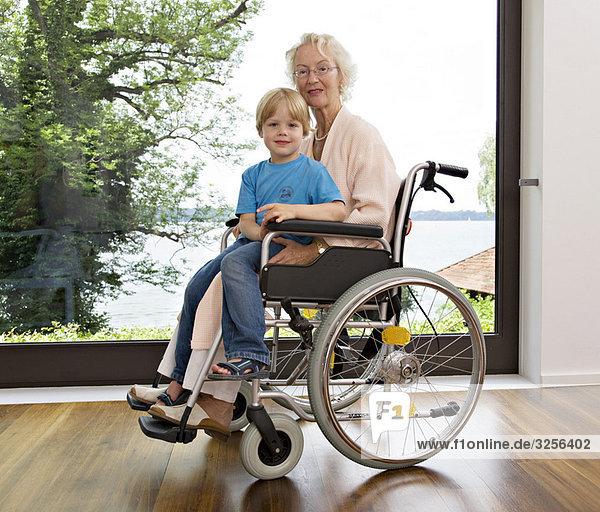 Junge auf dem Schoß einer älteren Frau sitzend