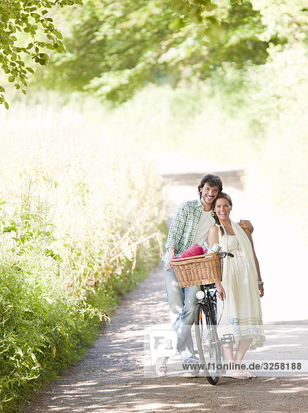 Man and woman with bike in country lane