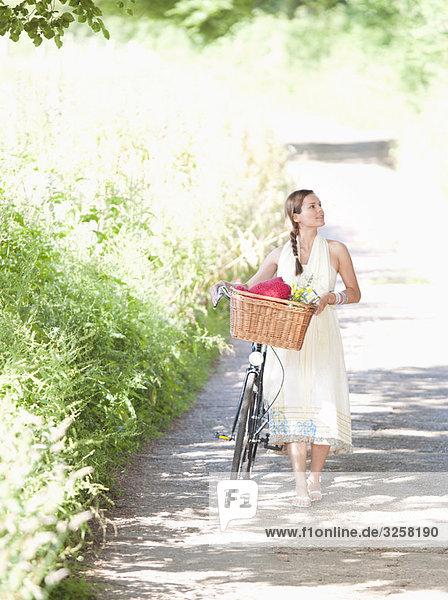 Woman walking with bike on country lane