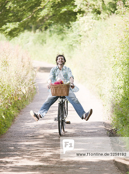 Man cycling in country lane