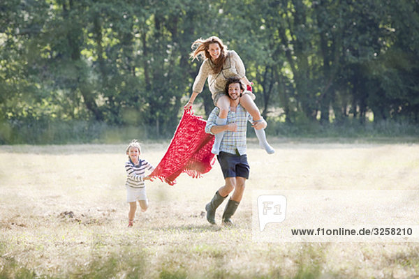 Family running in country field