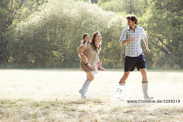 Family running together in country field