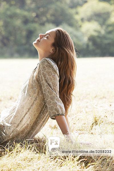 Woman lying back relaxing in field