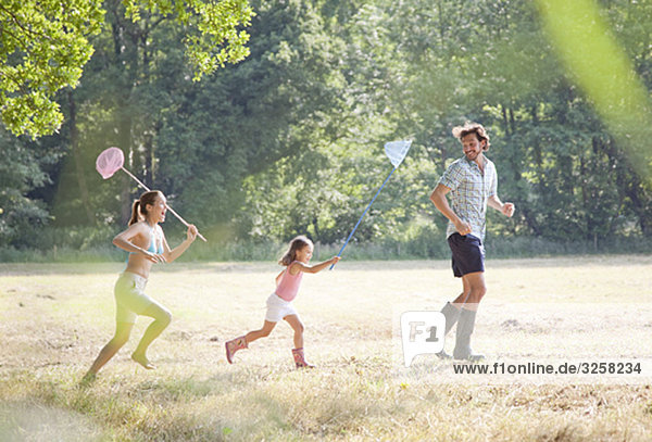 Family in countryside running with nets