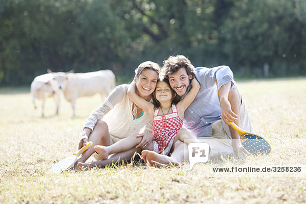 Family sitting laughing hugging in field