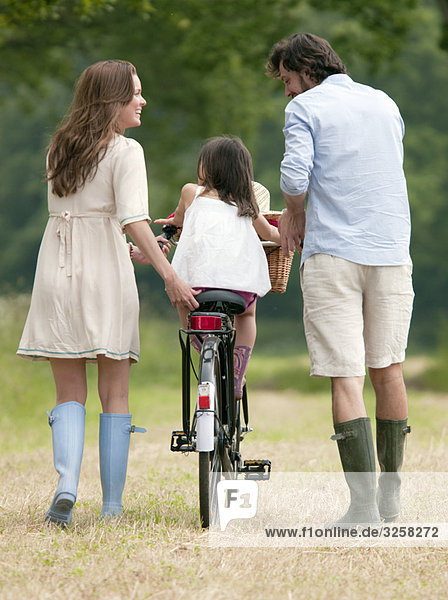 Family walking in country with bike