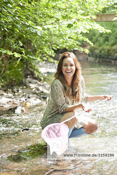 Woman in stream with fishing net