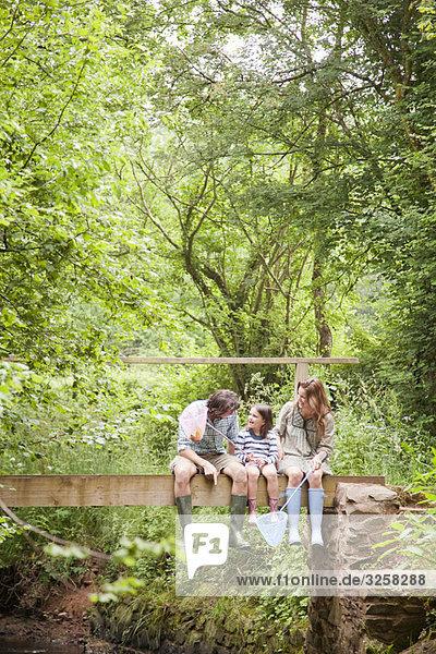 Family sitting talking on country bridge
