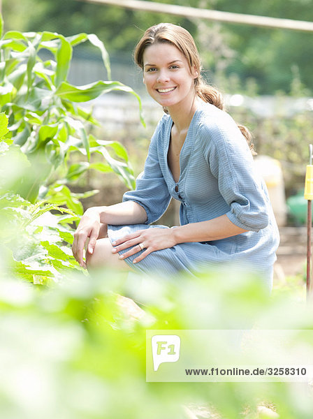 Woman kneeling around plants in country