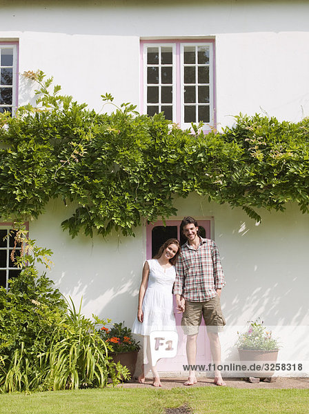 Man and woman standing in front of house
