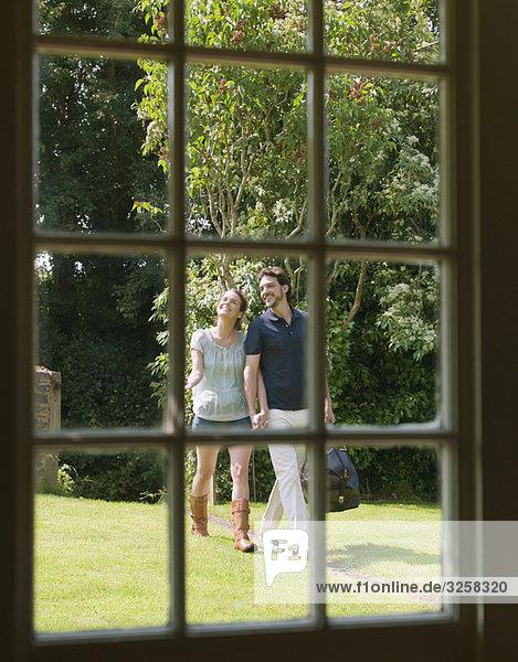 Man and woman walking down garden path
